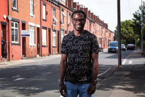 Participant Epie stands on a redbrick Leeds street