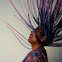 Participant Axelle tosses their braided hair in the air.