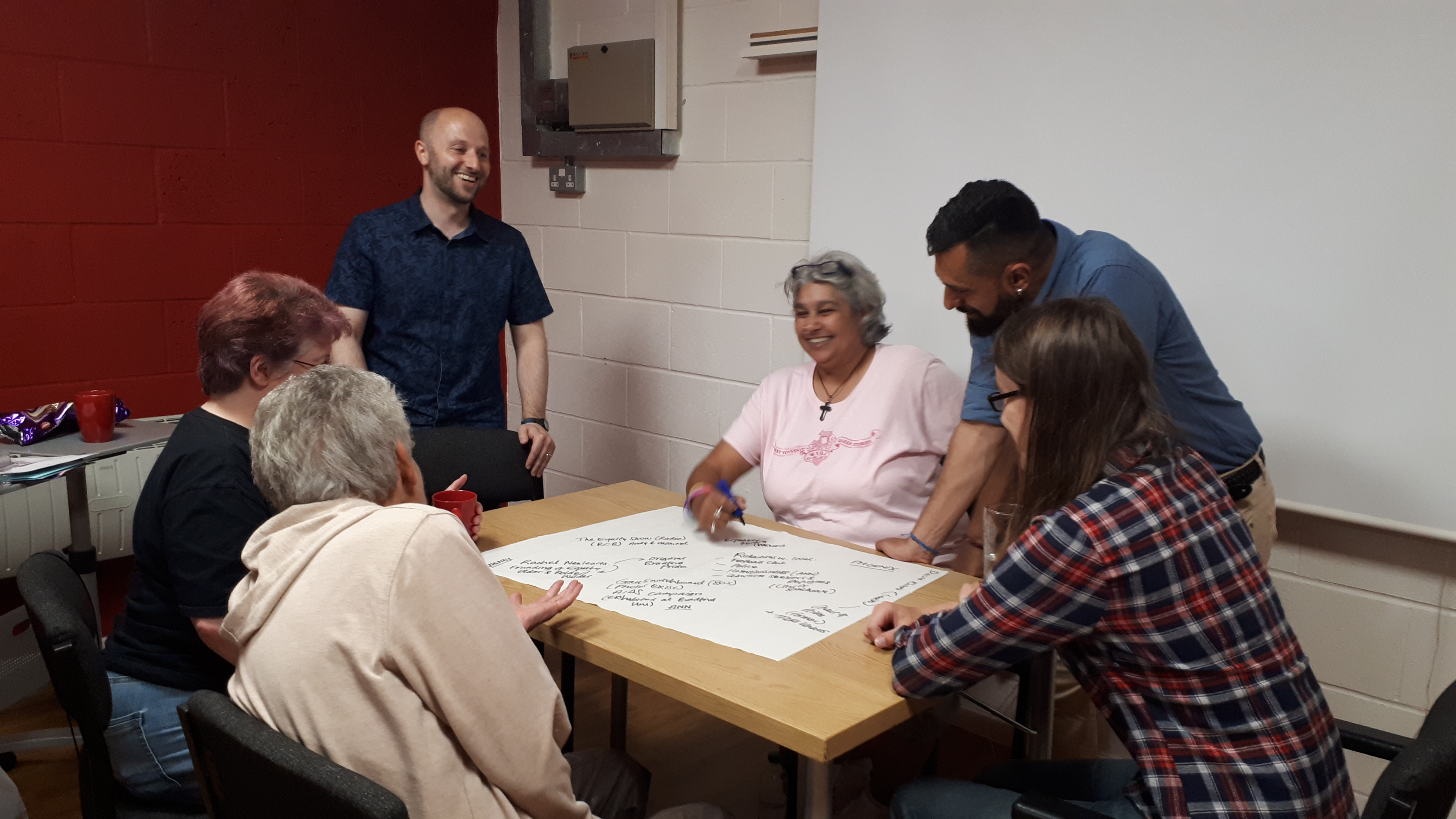 A community group gathers around a table writing on flip chart paper.