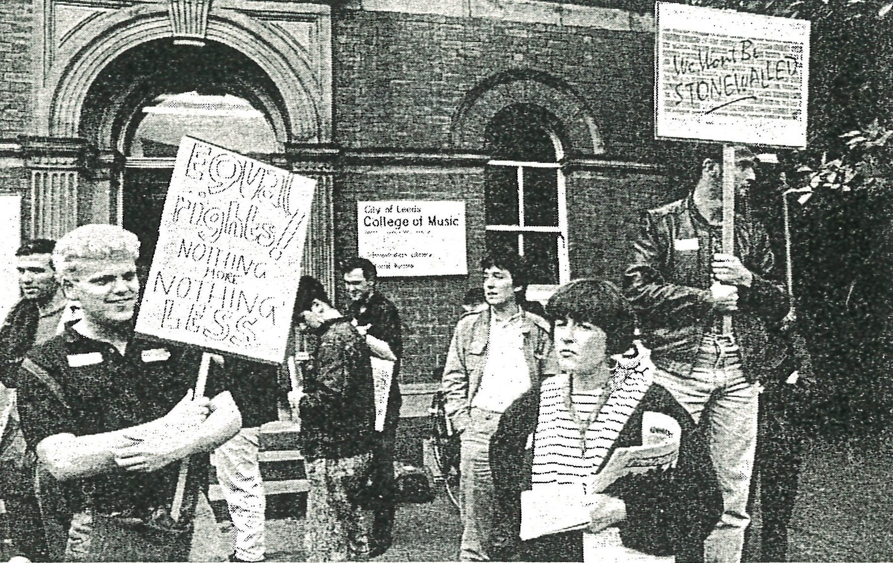 Old newspaper photo of people with placards protesting for equal rights outside Leeds College of Music.