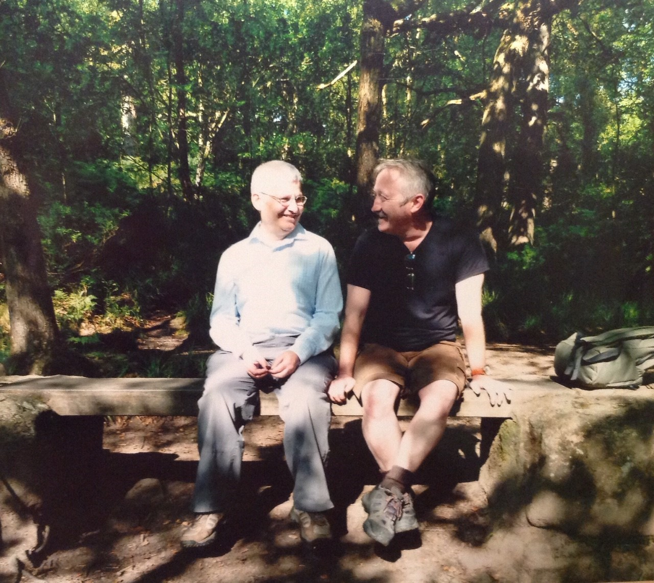 David and his partner Aram sit on a wooden bench in the woods