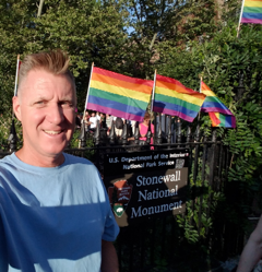 A man stands in front of a row of rainbow flags