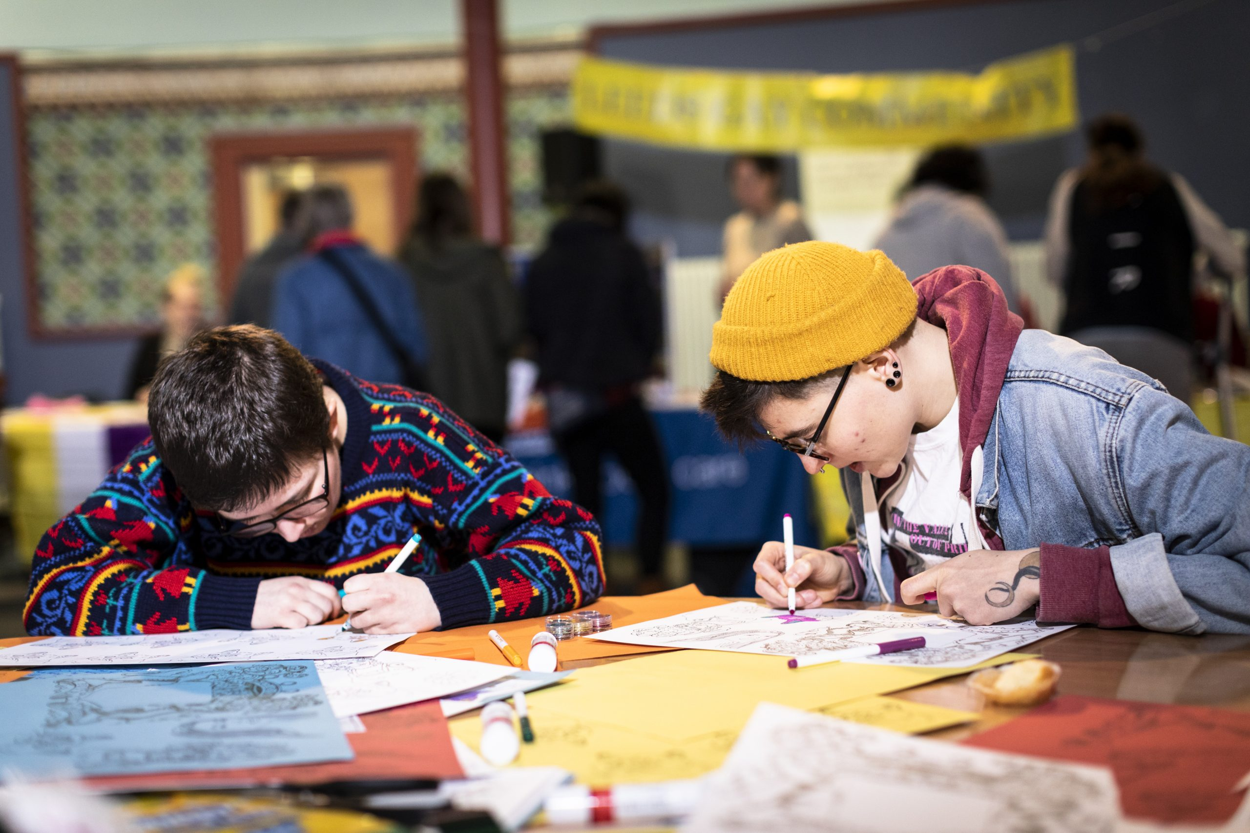Young people use pens to decorate the pages of a zine