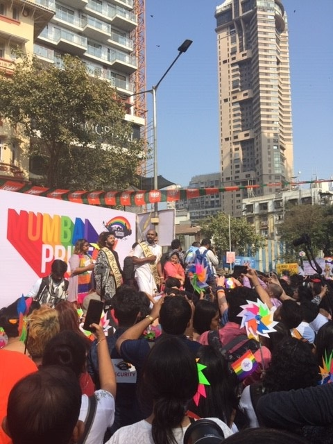 Performers stand in front of a rainbow sign that reads MUMBAI PRIDE
