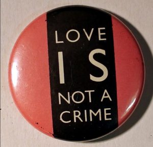 A badge with the slogan LOVE IS NOT A CRIME